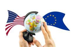 地球在欧盟和美国的旗子背景的手上  免版税库存图片