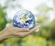 地球在绿色bokeh背景的手,这个图象的元素上 图库摄影
