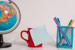 地球地图世界地球咖啡杯稠粘的笔记笔金属持有人说谎的减速火箭的葡萄酒土气老桌的正面图关闭 库存图片