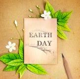 地球日与新春天绿色的纸板料生叶和花 免版税库存图片