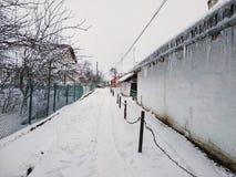 地球用雪,在雪,垂悬在老房子屋顶的冰柱的小径盖  冬天在乌克兰村庄 免版税库存照片