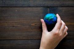 地球 递举行行星在黑暗的木背景顶视图拷贝空间的地球地球的plastiline标志 库存照片