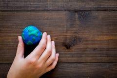地球 递举行行星在黑暗的木背景顶视图拷贝空间的地球地球的plastiline标志 免版税库存照片