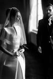 轻轻地看在面纱下的典雅的华美的新娘时髦的groo 免版税库存照片
