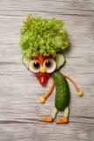 地精由新鲜蔬菜做成在木背景 库存图片