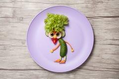 地精由新鲜蔬菜做成在板材和书桌 库存图片