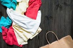 整洁地被折叠的衣裳和一个纸袋 库存图片
