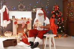 地道圣诞老人绘画玩具房子 免版税库存图片