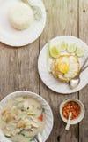 地道泰国晚餐背景:汤姆kha gai辣汤、简单的米和垫kra pao用煎蛋在顶面和自创辣椒sau 图库摄影
