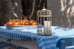 地道蜡烛灯笼和pommegranades在金属盘子在蓝色和白色在博兹贾岛Bozcaada Islandd stiped棉花桌布 免版税库存图片