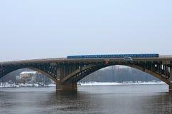 地铁有一列火车的地铁桥梁 地铁火车乘坐桥梁 小雪,冬天早晨 Kyiv,乌克兰 免版税库存图片
