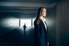 地铁隧道的美丽的孤独的妇女与吓唬剪影 库存照片