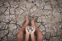 地面的人崩裂了干燥由于天旱 免版税库存照片