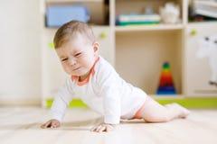 地面的逗人喜爱的哀伤的哭泣的婴孩在孩子屋子里 免版税库存照片