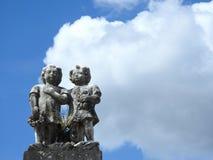场面在坟园:两个孩子老石雕象反对天空的与大云彩在一好日子 库存照片