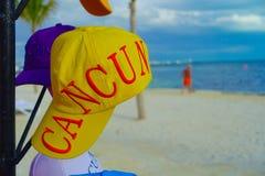 坎昆,墨西哥- 2018年1月10日:关闭有坎昆词的一个黄色体育帽子打印,与华美的白色沙子 免版税库存图片
