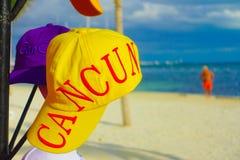 坎昆,墨西哥- 2018年1月10日:关闭有坎昆词的一个黄色体育帽子打印,与华美的白色沙子 免版税库存照片