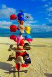 坎昆,墨西哥- 2018年1月10日:关闭被分类的体育帽子作为纪念品,与后边一个华美的白色沙子海滩 图库摄影