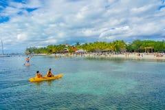 坎昆,墨西哥- 2018年1月10日:用浆划在他们的在一美丽的加勒比海滩isla的kayack的未认出的人民 免版税库存照片
