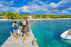 坎昆,墨西哥- 2018年1月10日:的未认出的游人走在Isla的一个木码头的美好的室外观点 免版税库存图片