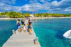 坎昆,墨西哥- 2018年1月10日:的未认出的游人走在Isla的一个木码头的美好的室外观点 免版税库存照片