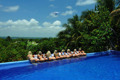 坎昆,墨西哥- 5月05 :模型由水池边缘白色T恤杉项目的摆在 免版税库存图片