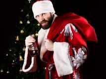 坏残酷圣诞老人运载一个袋子,微笑恶意和饮用的白兰地酒从一个瓶,在背景  图库摄影