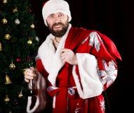 坏残酷圣诞老人运载一个袋子,微笑恶意和饮用的白兰地酒从一个瓶,在背景  库存图片