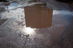 坏涂了柏油有一个大坑洼的路充满水 危险被毁坏的路基 库存照片