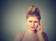 坏消息 画象不快乐的妇女谈话在看的手机下来 免版税图库摄影