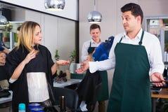 坏理发的女性责备的美发师 免版税库存图片