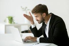 坏网上新闻失望的沮丧的商人 库存照片