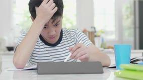 坏脾气的亚裔男孩做他的家庭作业使用片剂计算机找到信息 股票录像