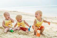 坐一个热带海滩在泰国和使用与沙子玩具的三小小孩 黄色衬衣 两个男孩和一个女孩 库存图片