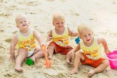 坐一个热带海滩在泰国和使用与沙子玩具的三小小孩 黄色衬衣 两个男孩和一个女孩 免版税图库摄影