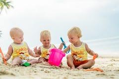 坐一个热带海滩在泰国和使用与沙子玩具的三小小孩 黄色衬衣 两个男孩和一个女孩 库存照片