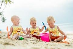 坐一个热带海滩在泰国和使用与沙子玩具的三小小孩 黄色衬衣 两个男孩和一个女孩 免版税库存图片