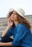 坐一个美好的女性的时装模特儿的画象户外 免版税库存图片