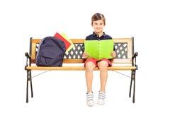 坐一个长木凳和读书的男小学生 免版税库存图片