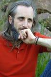 坐一个绿色背景晴天和考虑某事, potrait的有胡子的人 图库摄影