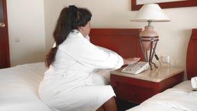 坐一张床在一件白色浴巾的一家旅馆里和打电话的不快乐的资深妇女 t 影视素材