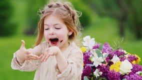 坐一张桌在公园并且吃一个甜蛋糕用她的手一个滑稽的smacky女孩的画象,巧克力踪影  影视素材