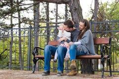 坐一条长凳在公园一起享受他们的时间的愉快的三口之家 免版税库存图片