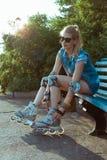 坐一条长凳在公园和投入在轴向冰鞋的直排轮式溜冰鞋的女孩在晴朗的明亮的光 体育生活方式 免版税库存照片