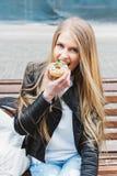 坐一条长凳在城市欧洲和吃鲜美五颜六色的多福饼的可爱的年轻白肤金发的性感的妇女 户外生活方式portra 免版税库存照片