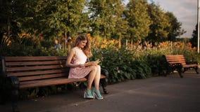 坐一条长凳在夏天公园和读书的美丽的年轻白肤金发的妇女 影视素材