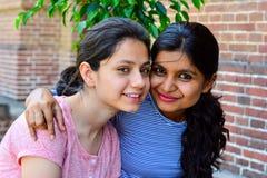 坐一起微笑和看的两个美丽的印度女孩照相机 免版税图库摄影
