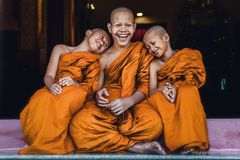 坐一起感到愉快和微笑的佛教新手 库存图片