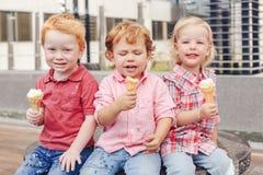 坐三个白白种人逗人喜爱的可爱的滑稽的儿童的小孩一起分享冰淇凌 免版税图库摄影
