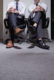 坐下与腿的两个商人横渡了,低部分 免版税库存图片